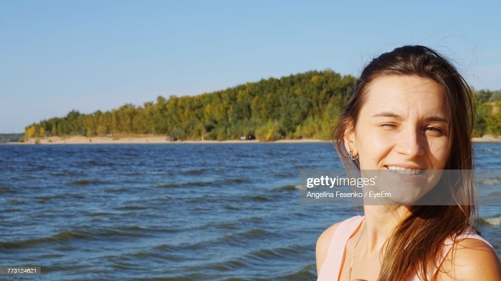 Close-Up Portrait Of Smiling Woman Against Sea : Photo