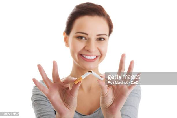 Close-Up Portrait Of Smiling Woman Breaking Cigarette Against White Background