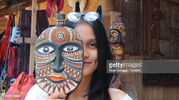 close-up portrait of smiling woman holding antique - rantepao stock photos and pictures