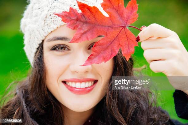 Close-Up Portrait Of Smiling Woman Holding Red Leaf