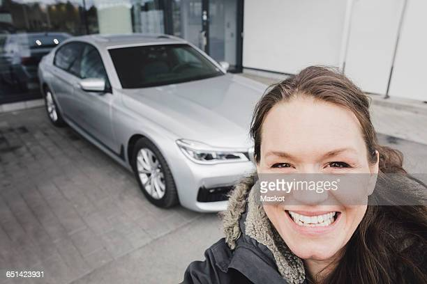 Close-up portrait of smiling woman standing against car outside showroom