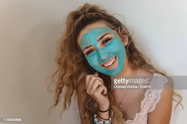 close-up portrait of smiling woman wearing blue face mask at home - chelsea mask stock pictures, royalty-free photos & images