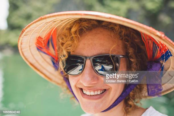 Close-Up Portrait Of Smiling Woman Wearing Sunglasses And Hat