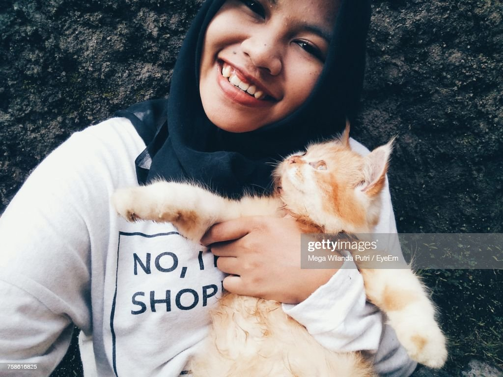 Close-Up Portrait Of Smiling Woman With Cat Against Wall : Photo