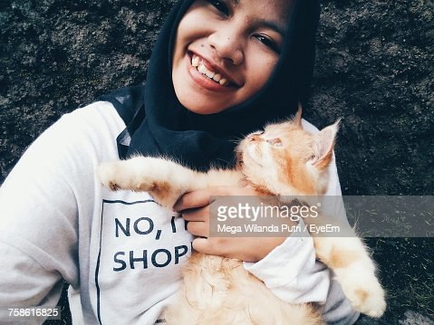 Close-Up Portrait Of Smiling Woman With Cat Against Wall