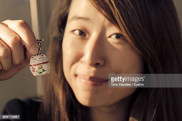 Close-Up Portrait Of Smiling Young Woman Holding Cat Key Ring