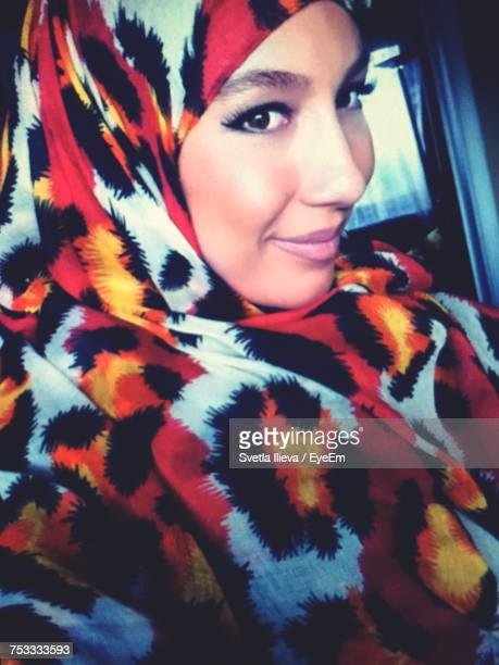 Close-Up Portrait Of Smiling Young Woman Wearing Hijab In Car