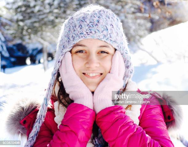 Close-Up Portrait Of Smiling Young Woman Wearing Warm Clothing During Winter