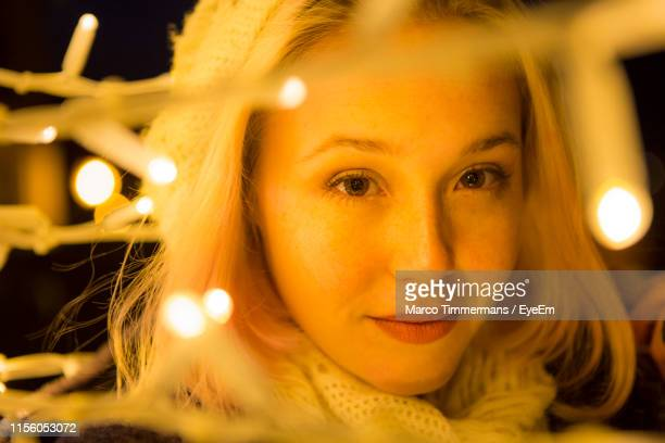 close-up portrait of smiling young woman with illuminated string lights at night - dordrecht stock pictures, royalty-free photos & images