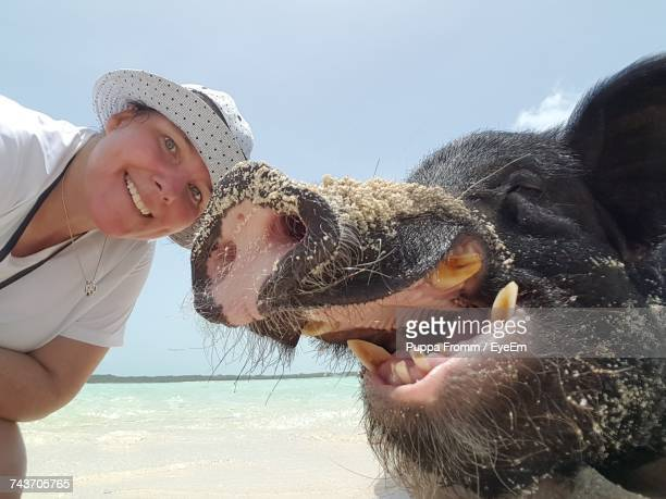 Close-Up Portrait Of Smiling Young Woman With Pig Against Sky