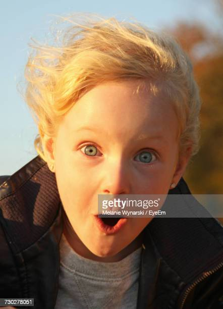 close-up portrait of surprised girl against sky - grey eyes stock pictures, royalty-free photos & images