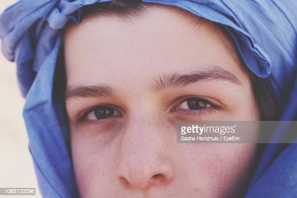 close-up portrait of teenage boy wearing headscarf - north africa stock photos and pictures