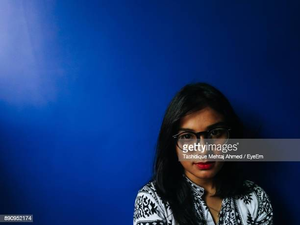 close-up portrait of teenage girl wearing eyeglasses against blue wall - one teenage girl only stock pictures, royalty-free photos & images