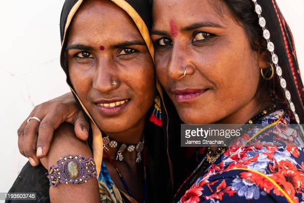 close-up portrait of two attractive rajasthani women sisters in brightly coloured traditional dress, arms around each other, cheek to cheek, against white background, pushkar, rajasthan, india (two model releases) - james strachan stock pictures, royalty-free photos & images