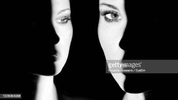 close-up portrait of woman against black background - scary face stock photos and pictures