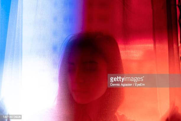 close-up portrait of woman against window - red stock pictures, royalty-free photos & images