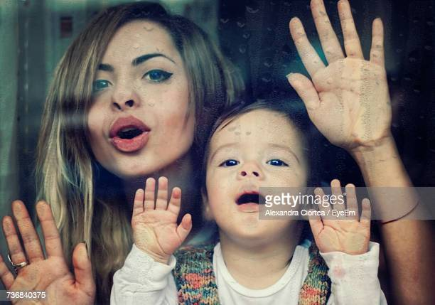 Close-Up Portrait Of Woman And Girl Behind Window