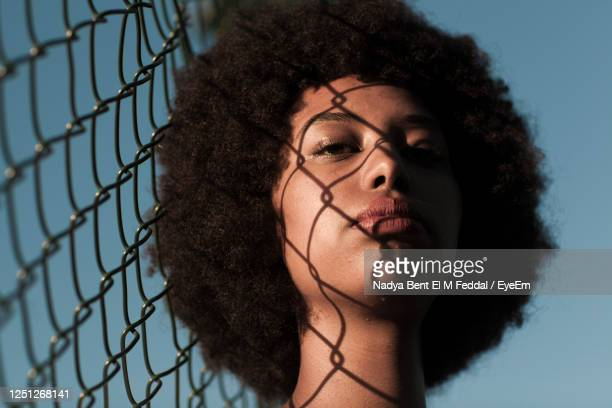 close-up portrait of woman by chainlink fence against sky - fence stock pictures, royalty-free photos & images