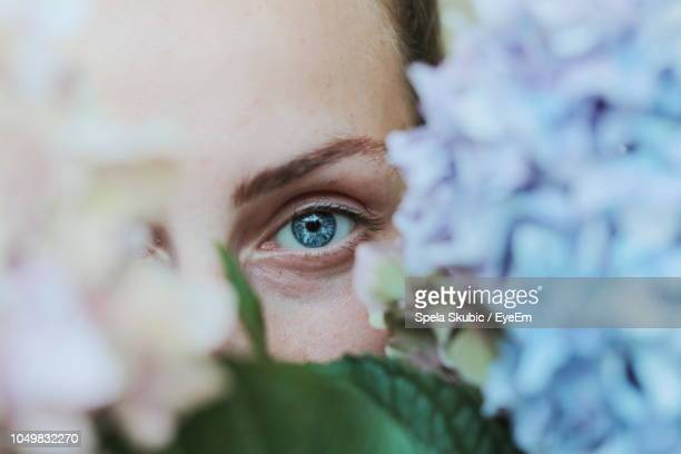Close-Up Portrait Of Woman By Flowers