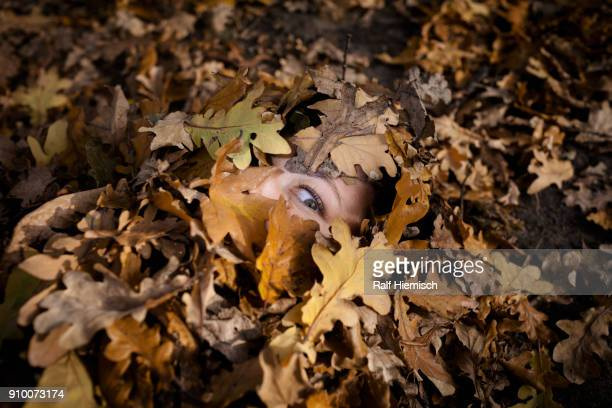 Close-up portrait of woman covered in dry leaves during autumn