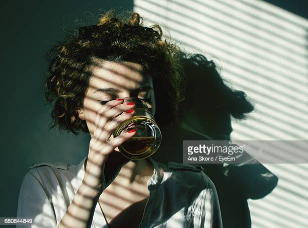 Close-Up Portrait Of Woman Drinking
