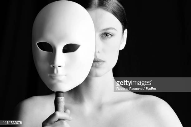 close-up portrait of woman holding mask against black background - mask disguise stock pictures, royalty-free photos & images