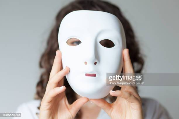 close-up portrait of woman holding mask against white background - face masks imagens e fotografias de stock