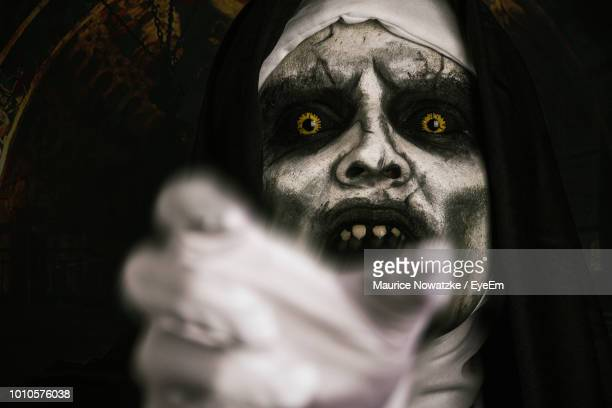 close-up portrait of woman in demon nun costume gesturing at night - demons stock photos and pictures