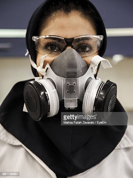 Close-Up Portrait Of Woman In Gas Mask At Laboratory