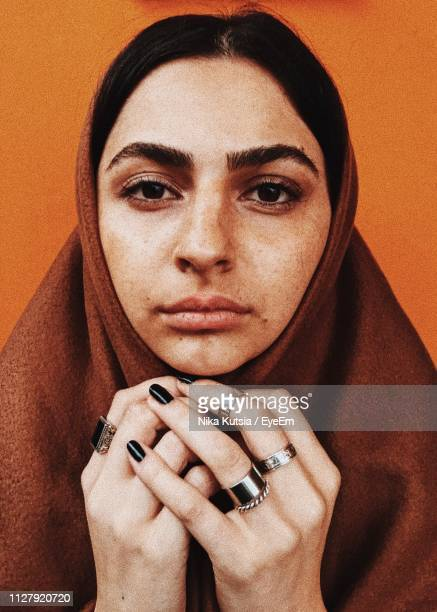 close-up portrait of woman in hijab against orange background - no make up stock pictures, royalty-free photos & images