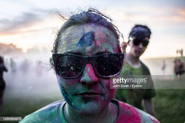 close-up portrait of woman in sunglasses covered with powder paint - festival goer stock pictures, royalty-free photos & images