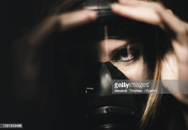 close-up portrait of woman in the dark - looking at camera stock pictures, royalty-free photos & images