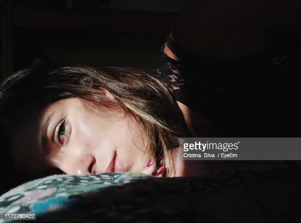 close-up portrait of woman lying on bed at home - sdraiato foto e immagini stock