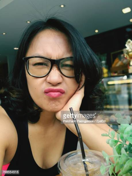 close-up portrait of woman making face while sitting with drink at coffee shop - coffee drink stock pictures, royalty-free photos & images