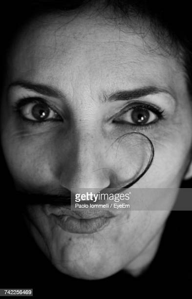 Close-Up Portrait Of Woman Making Mustache With Hair In Darkroom