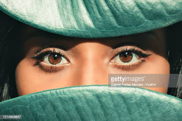 close-up portrait of woman seen through leaves - eye liner stock pictures, royalty-free photos & images