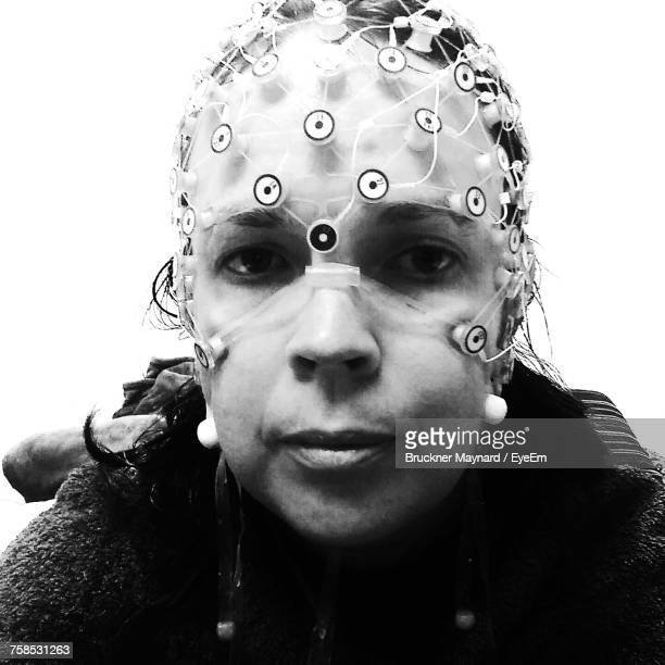 Close-Up Portrait Of Woman Wearing Eeg Against Wall At Home
