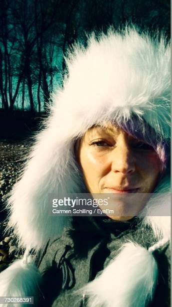 Close-Up Portrait Of Woman Wearing Fur Hat On Sunny Day