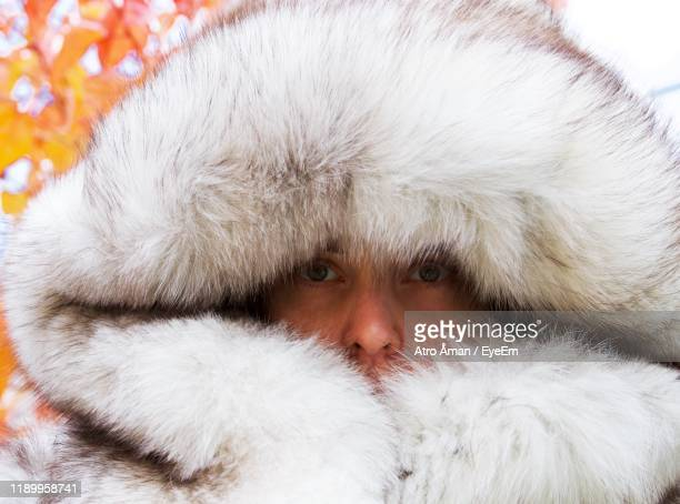 close-up portrait of woman wearing fur hooded coat against plants - fur coat stock pictures, royalty-free photos & images