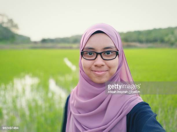 Close-Up Portrait Of Woman Wearing Hijab Against Rice Paddy