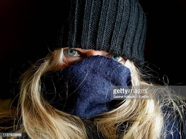 close-up portrait of woman wearing mask against black background - black mask disguise stock pictures, royalty-free photos & images