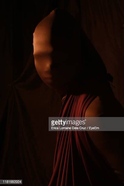 close-up portrait of woman wearing mask while standing against black background - lorraine smothers stock pictures, royalty-free photos & images