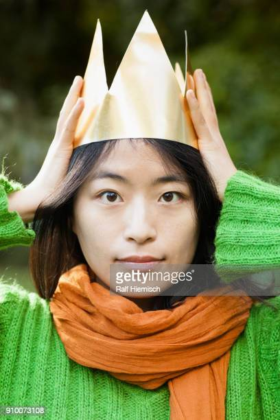 Close-up portrait of woman wearing paper crown at park