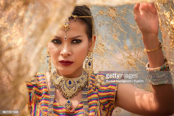 close-up portrait of woman wearing sari and jewelry against fabric - sari stock pictures, royalty-free photos & images