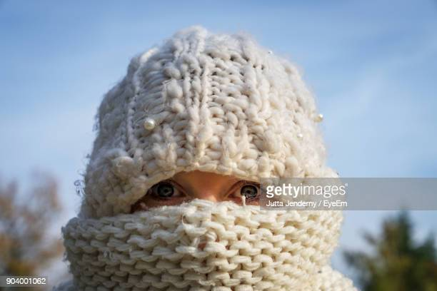 close-up portrait of woman wearing scarf on face against sky - schal stock-fotos und bilder