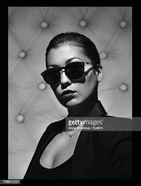 Close-Up Portrait Of Woman Wearing Sunglasses Against Abstract Background