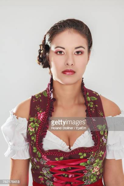 Close-Up Portrait Of Woman Wearing Traditional Clothing Against White Background