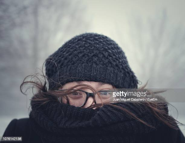 close-up portrait of woman wearing warm clothing during winter - abiti pesanti foto e immagini stock
