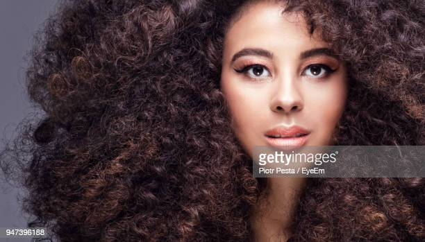 close-up portrait of woman with curly hair against gray background - big hair stock photos and pictures