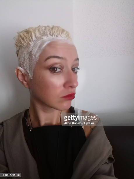 close-up portrait of woman with dyed hair against wall at home - hair colourant stock pictures, royalty-free photos & images